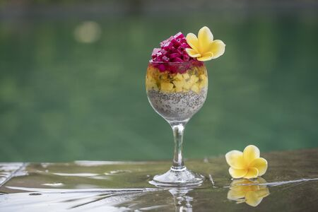 Chia seeds pudding with red dragon fruit and white yogurt in a glass for breakfast on the background of the swimming pool water, close up. The concept of healthy eating.