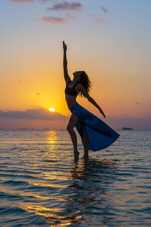 Young beauty girl dancing at tropical beach on sea water at paradise island at sunset, close up. Summer concept. Holiday travel.