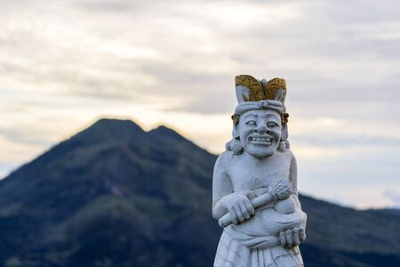 Traditional Balinese sculpture against the background of the volcano Batur on sunrise, morning time. Island Bali, Indonesia. Close up Stockfoto