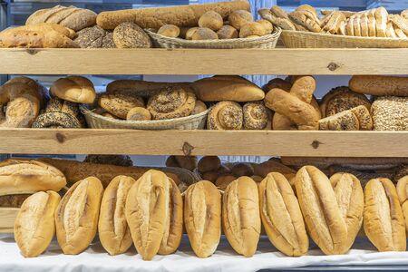 Boulangerie moderne avec assortiment de pain sur étagère, gros plan. Notion de nourriture. Variété de produits de boulangerie au magasin de pain