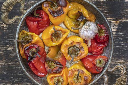 Pimientos morrones rojos y amarillos al horno. Pimientos en una fuente para hornear sobre una mesa de madera. Un plato vegetariano sano y delicioso. De cerca, vista superior Foto de archivo
