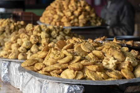 Heap of fried indian samosa on buffet table in local street market, India. Indian food close up