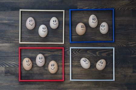 Picture frame and many funny eggs smiling on dark wooden wall background, close up. Eggs family emotion face portrait. Concept funny food