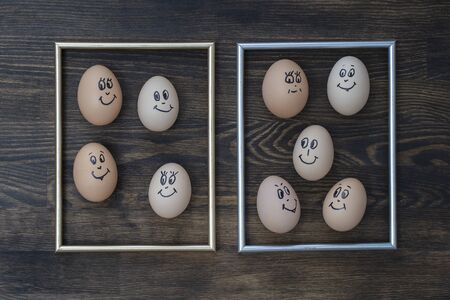 Picture golden frame and many funny eggs smiling on dark wooden wall background, close up. Eggs family emotion face portrait. Concept funny food