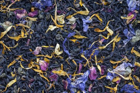 Dry herbs tea with fruit and flower petals as background, top view. Healthy eating concept