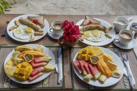 Tropical breakfast of fruit, coffee and scrambled eggs and banana pancake for two on the beach near sea in hotel restaurant, island Zanzibar, Tanzania, Africa, close up Archivio Fotografico - 138043467