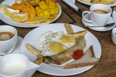 Tropical breakfast of fruit, coffee and scrambled eggs and banana pancake for two on the beach near sea in hotel restaurant, island Zanzibar, Tanzania, Africa, close up Archivio Fotografico - 138043473
