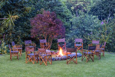 View of the burning bonfire together around it with chairs on the green lawn near the forest, Tanzania, East Africa