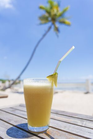 Pineapple juice in glass on the tropical beach near sea, close up. Travel and vacation concept