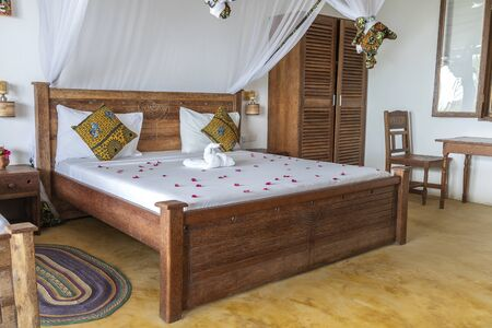 Interior design decor furnishing of luxury show home holiday villa bedroom with four poster bed. Interior design of the tropical villa on the sea on the island of Zanzibar, Tanzania, East Africa
