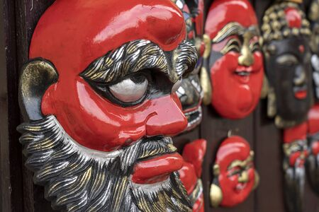 Traditional wooden masks hanging for sell on the street market in Hanoi, Vietnam, close up 免版税图像