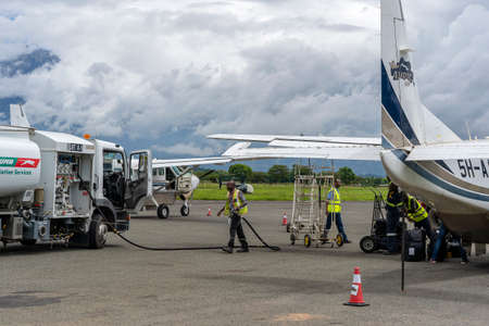 Arusha, Tanzania - december 28, 2019 : Fuel truck refueling small propeller airplane before takeoff at Arusha airport, Tanzania, east Africa