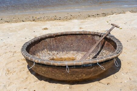 Close up, traditional Vietnamese boat placed on a tropical beach located in Cu Lao Cham island near Danang, Vietnam. This round basket boat is made of woven bamboo. It is also called Thung Chai. Imagens