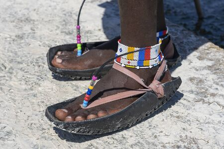 Tribal masai legs with a colorful bracelet and sandals made of car tires on the sand beach, close up. Island of Zanzibar, Tanzania, East Africa