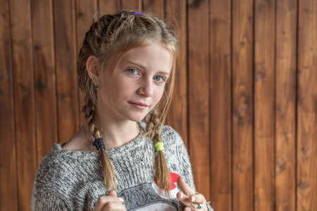 Beautiful blonde young girl with freckles indoors on wooden background, close up portrait Banque d'images