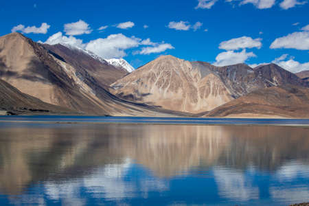 View of majestic rocky mountains against the blue sky and lake Pangong in Indian Himalayas, Ladakh region, Jammu and Kashmir, India. Nature and travel concept