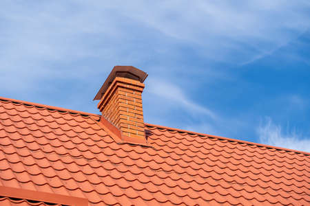 Red roof of a detached house and chimney against the blue sky, close up