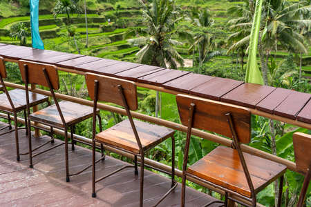 Wooden table and chairs in empty tropical cafe next to rice terraces in island Bali, Indonesia, close up