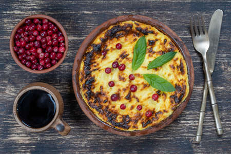 Sweet cottage cheese casserole with raisins and semolina on wooden table. Ceramic bowl with baked cottage cheese casserole, close up, top view