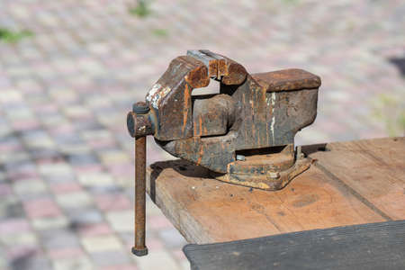 Old rusty vise for metal products on wooden table, outdoors, close up