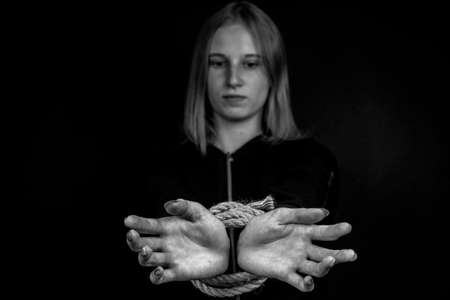 Portrait of young girl with bound hands on black background. Black and white