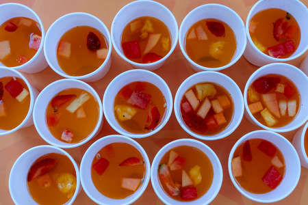 Lots of sweet fruit lemonade from red strawberries, melons and pineapple in a in white cups. Close up. Refreshing drink from pieces of fruit, top view