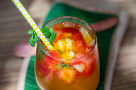 Fruit lemonade from red strawberries, melons and pineapple in a glass. Close up. Refreshing drink from pieces of fruit Zdjęcie Seryjne