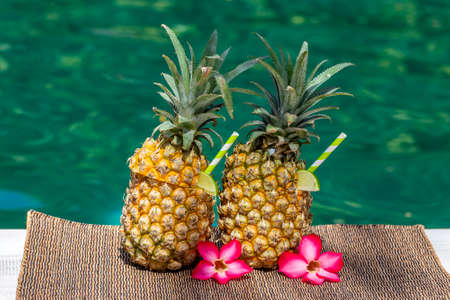 Pina colada cocktail in fresh two pineapples fruits near swimming pool, close up. Island Bali, Indonesia