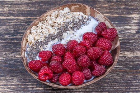 Smoothie in coconut bowl with raspberries, oatmeal and chia seeds for breakfast, close up. The concept of healthy eating, superfood. Top view