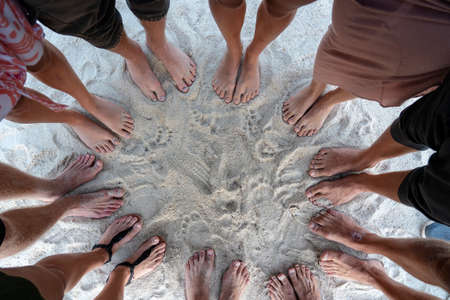 Many female and male legs are standing together on sand near the sea, summer holidays concept. Top view feet of people or group of friends on the beach 스톡 콘텐츠