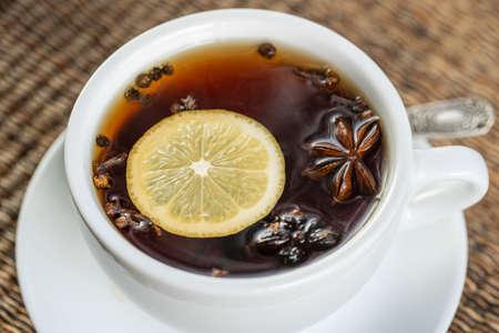 Spice tea, consisting of cinnamon, black pepper, cardamom, star anise, lemon, cloves and hot apple juice. Close up, top view. Cinnamon tea. Tea drink