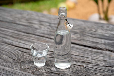Bottle and glass with water on the wooden table, close up