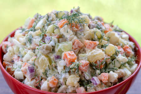 Healthy homemade russian traditional salad olivier ready to eat, close up, top view