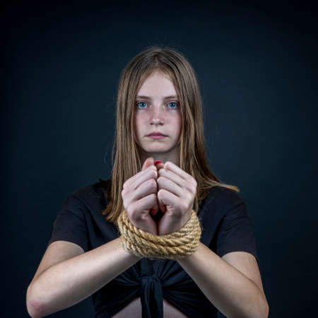Portrait of young girl with bound hands on black background. Close up