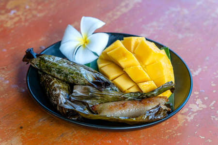 Thai style dessert, yellow mango with banana sticky rice in palm leaves. Yellow mango and sticky rice is popular traditional dessert of Thailand. Close up
