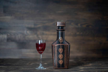 Homemade tincture of red cherry in a decorative bottles and a wineglass on wooden background, Ukraine, close up