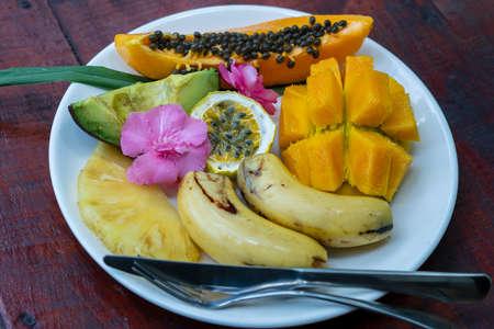 Tropical fruits on a white plate, close up. Fresh mango, banana, avocado, papaya, passion fruit, pineapple on a plate, Zanzibar, Tanzania, east Africa