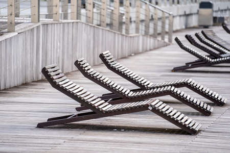 Wooden empty deck chairs on the promenade