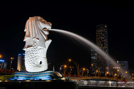 Singapore city, Singapore - february 26, 2020: Merlion statue spraying the water from its mouth at Merlion Park in downtown core of Singapore at Marina Bay at night time 新聞圖片