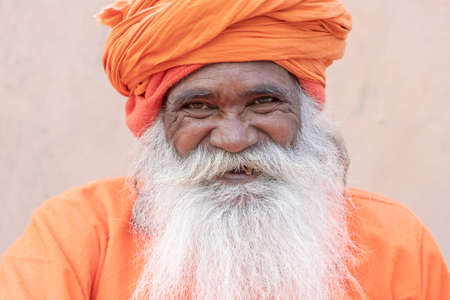 RISHIKESH, INDIA - NOVEMBER 05, 2018: Unidentified Hindu sadhu holy man, sits on the ghat near the Ganges river in Rishikesh, India, close up