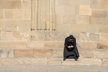MTSKHETA, GEORGIA - OCTOBER 27, 2018: lonely old monk in black clothes sits on the stairs on a sunny day near the old orthodox cathedral in historical town Mtskheta near Tbilisi, Georgia Redactioneel