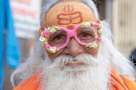 PUSHKAR, INDIA - NOVEMBER 16, 2018: Hindu sadhu, holy man in pink glasses, sits on the ghat near lake in Pushkar, India, close up portrait