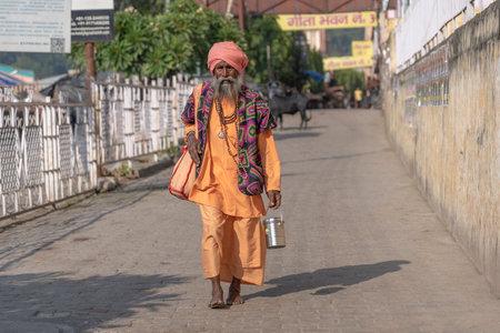 RISHIKESH, INDIA - NOVEMBER 06, 2018: Unidentified Hindu sadhu holy man walks down the street next to the ghat near the Ganges river in Rishikesh, India, close up