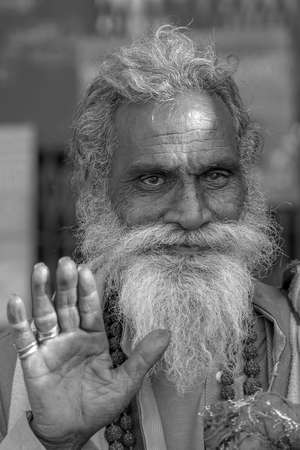 RISHIKESH, INDIA - NOVEMBER 06, 2018: Portrait of Hindu sadhu holy man, sits on the ghat and asks for alms from passers-by near the Ganges river in Rishikesh, India, close up. Black and white