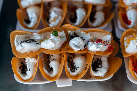 Delicious Thai street dessert, Kanom Buang, Thai Crispy Pancake or Thai Crepe, with varieties of fillings such as sweet white custard cream and golden sweet egg floss or salty minced shrimp on fry pan