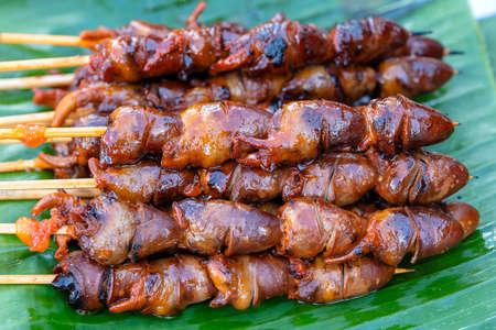 Thai street vendor sells grilled chicken hearts at street food market in island Koh Phangan, Thailand. Close up Imagens