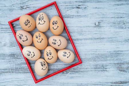 Picture red frame and many funny eggs smiling on white wooden wall background, close up. Eggs family emotion face portrait. Concept funny food. Copy space