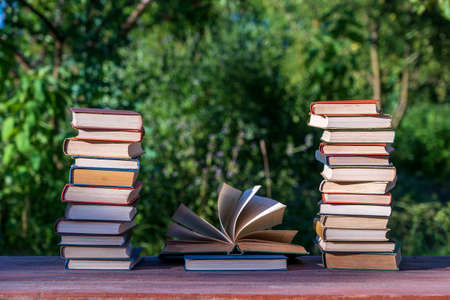 Stack of books on wooden table over nature background, outdoors, close up