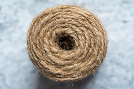 High-quality handmade coil made of natural hemp rope, isolated on a white background. Rustic beige cord made of eco material