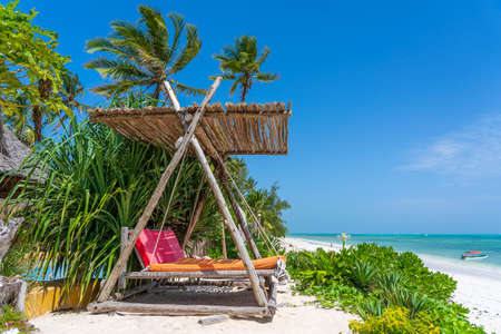 Wooden swing with a mattress under a canopy on the tropical beach near sea, island Zanzibar, Tanzania, East Africa, travel and vacation concept
